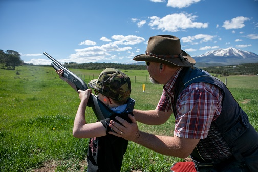Youth shooting shotgun with instructor