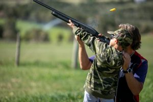 Youth assited by instructors hit moving clay targets with shotguns